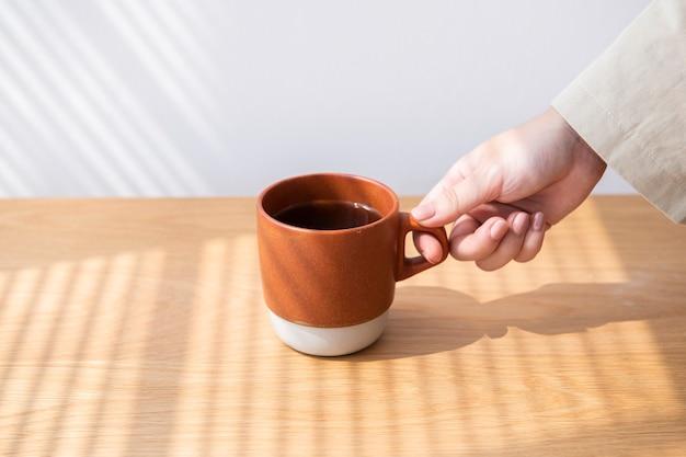 Mulher pegando uma xícara de café em uma mesa de madeira