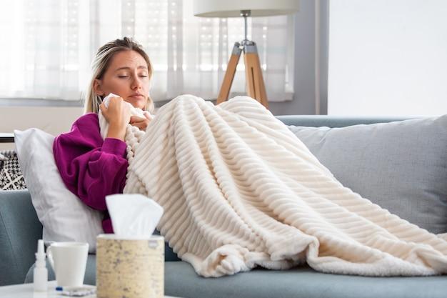 Mulher pegou resfriado e gripe espirros no tecido.