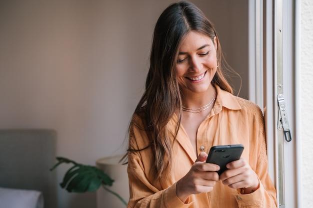 Mulher pela janela em casa usando telefone celular