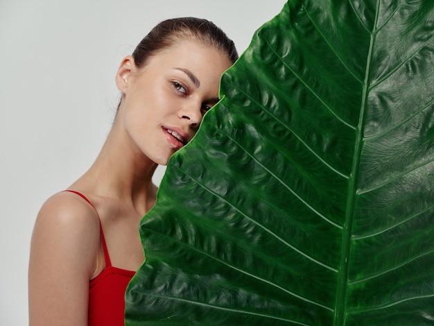 Mulher pele limpa folha de palmeira verde modelo de aparência natural