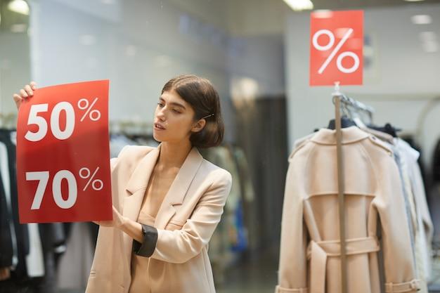 Mulher pendurada sinais de venda na loja