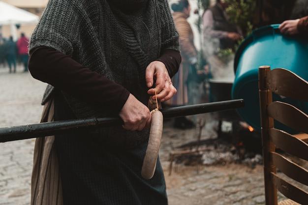 Mulher pendurando kielbasa em um cano cercada de pessoas
