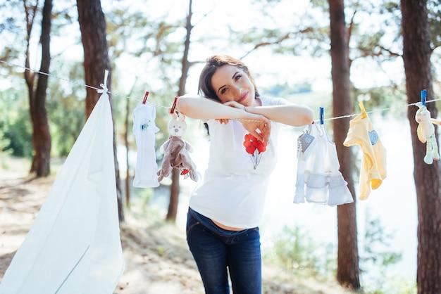 Mulher pendurando roupas de bebê em corda de linho ao ar livre