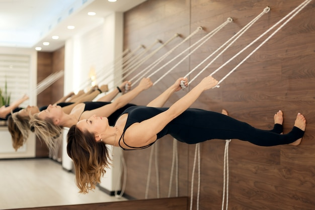 Mulher, pendurar, varal, paralelo, para, a, chão, prática, ioga, ligado, esticar marca, em, ginásio