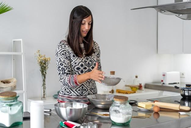 Mulher peneirando a farinha em uma tigela