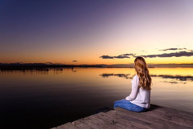 Mulher pensa com calma em uma bela paisagem de outono ao pôr do sol com tons quentes