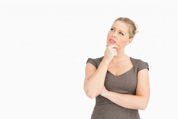 Mulher pensando com um dedo no rosto