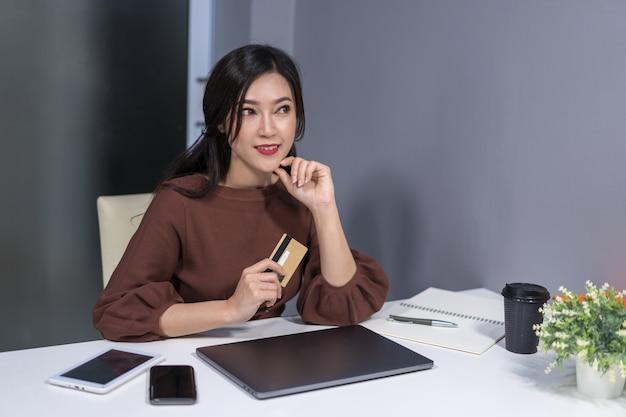 Mulher, pensando, e, segurando, cartão crédito, com, laptop, ligado, tabela
