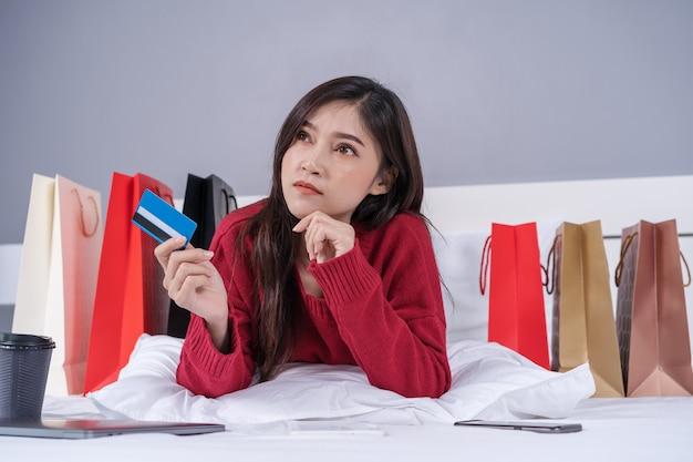 Mulher pensando e usando tablet digital para compras on-line com cartão de crédito na cama