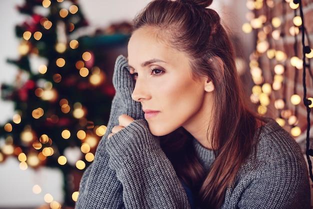 Mulher pensando em casa com luzes de natal na parede