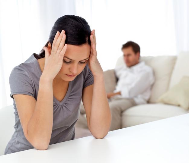 Mulher pensando em uma mesa enquanto seu namorado se relaxava no sofá