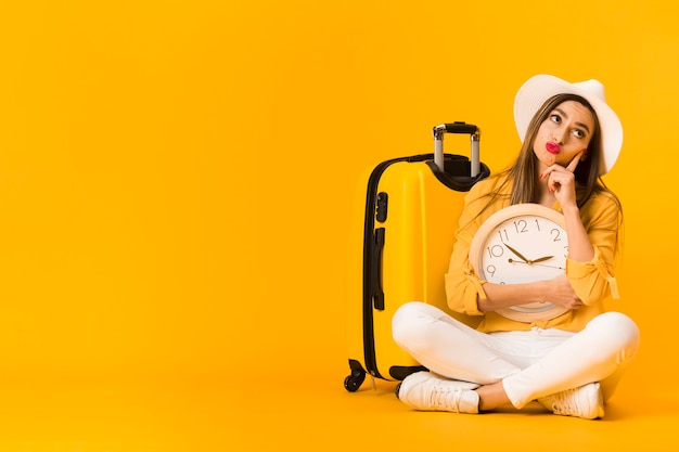 Mulher pensando enquanto segura o relógio ao lado de bagagem com espaço de cópia