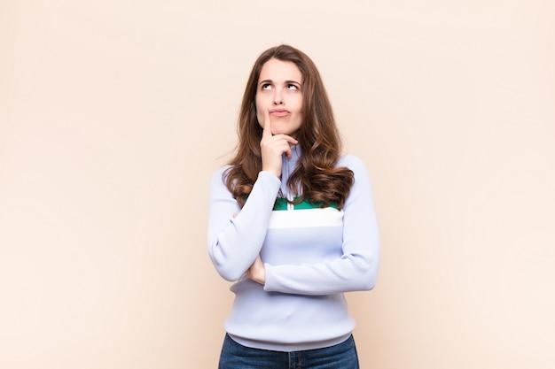 Mulher pensando, sentindo-se duvidosa e confusa, com diferentes opções, imaginando qual decisão tomar
