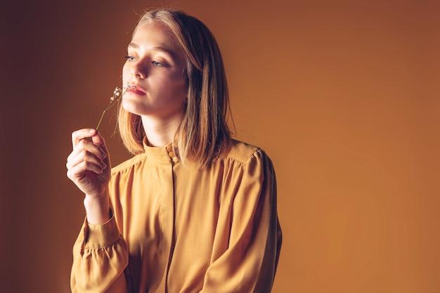 Mulher pensativa, cheirando a flor