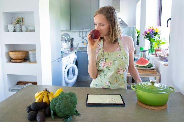 Mulher pensativa cheirando frutas enquanto cozinha na cozinha, usando o tablet perto da panela e legumes frescos no balcão. vista frontal. cozinhando em casa e conceito de alimentação saudável