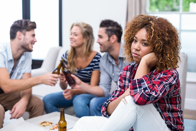 Mulher pensativa com amigos desfrutando de cerveja