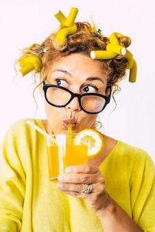 Mulher pensativa com bobes de cabelo bebendo um copo de suco jovem aplicando bobes no cabelo