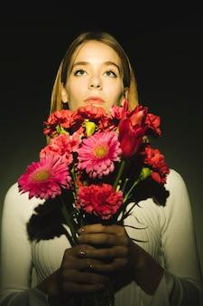 Mulher pensativa com buquê de flores brilhantes