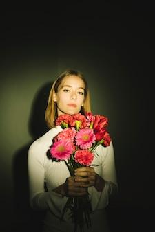 Mulher pensativa com buquê de flores cor de rosa