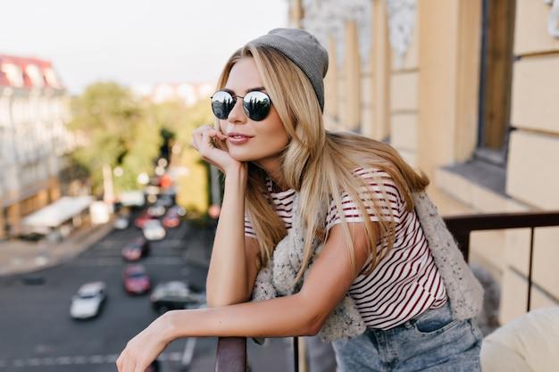 Mulher pensativa com cabelo dourado brilhante olhando para longe com um sorriso na varanda