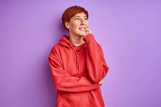 Mulher pensativa com cabelo vermelho fica pensando olhando para cima, conceito de pessoas e emoções humanas