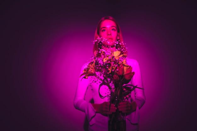 Mulher pensativa com flores brilhantes em vaso