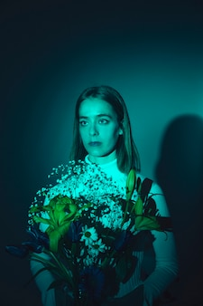 Mulher pensativa com flores brilhantes