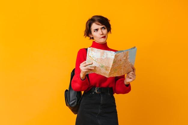 Mulher pensativa com mapa olhando para longe