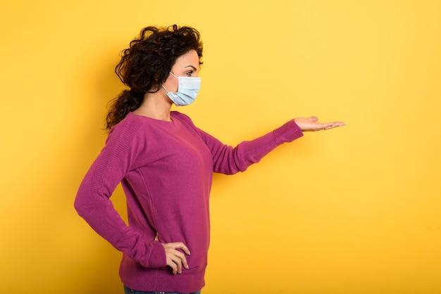 Mulher pensativa com máscara facial segura algo na mão.