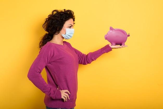 Mulher pensativa com máscara facial segura um cofrinho. conceito de banco de depósito de dinheiro.