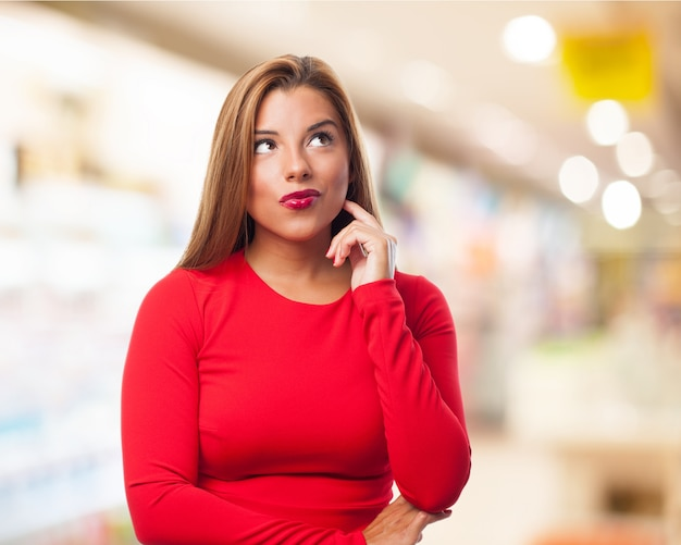 Mulher pensativa com os lábios pintados de vermelho