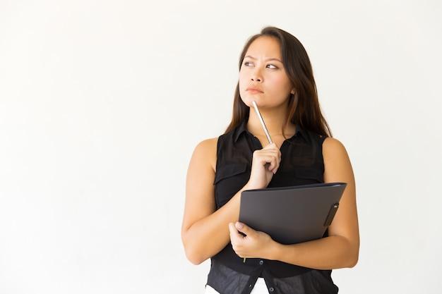 Mulher pensativa com pasta e caneta