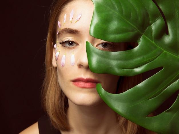 Mulher pensativa com pétalas de flores no rosto e folha verde