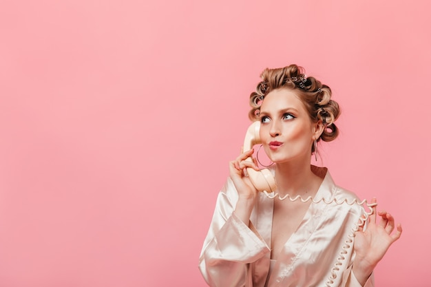 Mulher pensativa com robe de seda falando no telefone na parede isolada