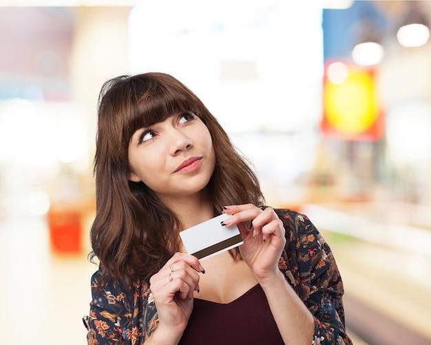 Mulher pensativa com um cartão de crédito