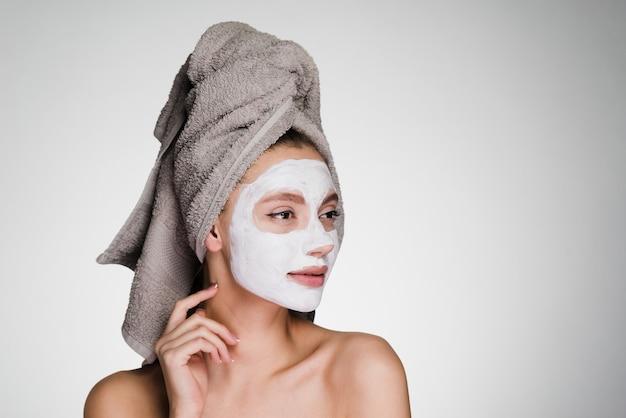 Mulher pensativa com uma toalha na cabeça após o banho aplicar máscara de limpeza no rosto