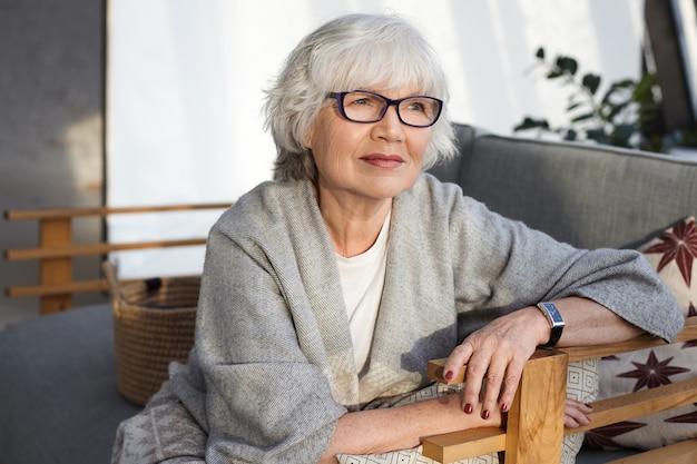 Mulher pensativa, de meia-idade, de cabelos grisalhos, usando óculos, lenço largo e relógio de pulso, passando o tempo de lazer em casa, sentada no confortável sofá da sala de estar, com olhar pensativo