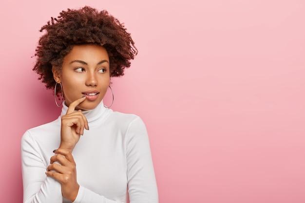 Mulher pensativa de pele morena com corte de cabelo afro, olha para o lado, contempla alguma coisa, veste suéter branco de poloneck, brincos grandes redondos, nota