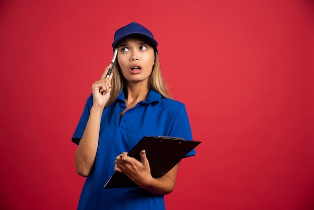 Mulher pensativa de uniforme azul, posando com prancheta e lápis.