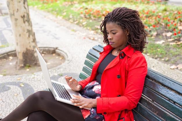 Mulher pensativa, digitando no laptop enquanto está sentado no banco no parque