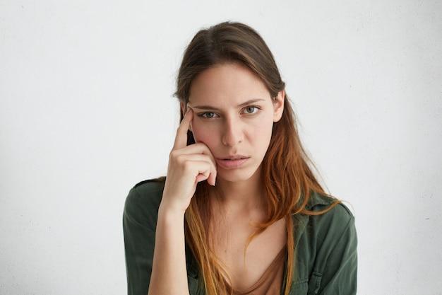 Mulher pensativa e cansada, com olhos escuros calorosos e cabelo liso, segurando o dedo indicador na têmpora, olhando sério