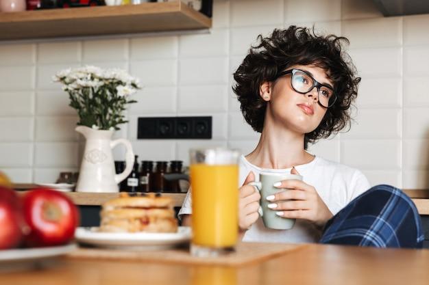 Mulher pensativa e muito encaracolada sentada na cozinha tomando chá