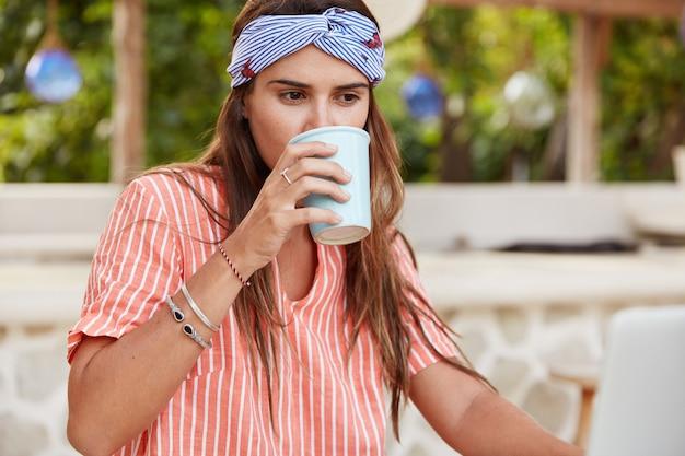 Mulher pensativa e satisfeita bebe café, está focada em algo, usa camisa casual listrada e bandana, descansa em um café ao ar livre.