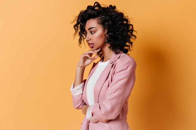 Mulher pensativa e sensual posando na parede amarela