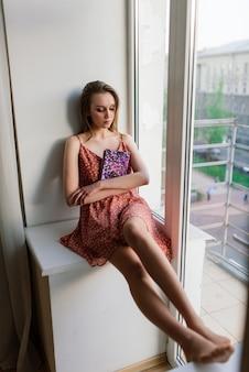 Mulher pensativa e sonhadora segurando o livro em casa, olhando para a grande janela, sonhando, jovem pensativa, estudante