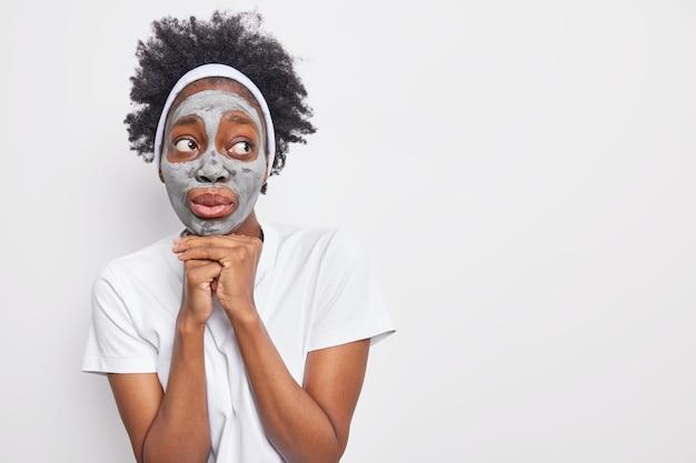 Mulher pensativa e surpresa com cabelo encaracolado mantém as mãos embaixo do queixo olhando para longe e aplica máscara de argila