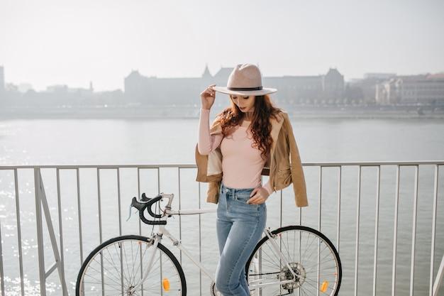 Mulher pensativa em jeans vintage olhando para baixo enquanto posa com bicicleta no aterro