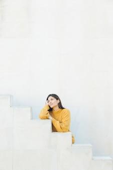 Mulher pensativa em pé contra a parede branca