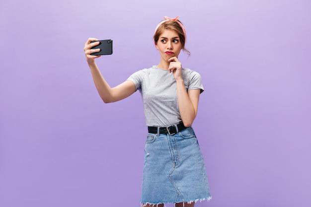 Mulher pensativa em saia jeans leva selfie sobre fundo roxo. rapariga com bandana rosa em t-shirt cinza faz foto.