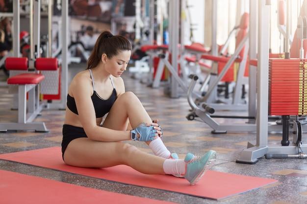 Mulher pensativa em sportswear sentado no tapete após o treino no ginásio, descansar depois do treino, parecendo cansado, usa sutiã e shorts esportivos elegantes